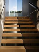 Narrow stairway with open wood steps wand black stone tiles on the wall