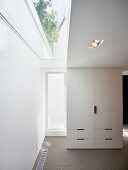 Free standing white cupboard next to a patio door and skylight strips in the ceiling