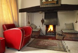 A red leather armchair in front of a fire