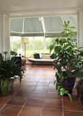 A view into a conservatory with a daybed and terracotta tiles