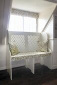 Decorative cushions on a white bench with a patterned seat in front of a window