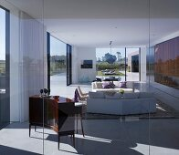 South American house with view across wide landscape through glass walls of living room with sofas and elegant, curved cabinet
