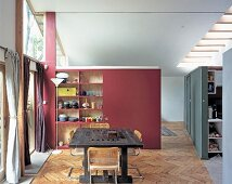 Red room divider with built-in shelves and rustic workbench in front of a bank of windows