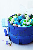 Easter eggs and butterflies in a blue basket
