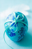 A turquoise Easter egg tied with ribbon