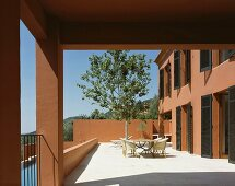Sun-drenched terrace with table and chairs in front of a tree and a Mediterranean home with a reddish brown facade