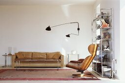Armchair and wall lamp in Bauhaus style in front of a light brown leather sofa in the corner of a living room
