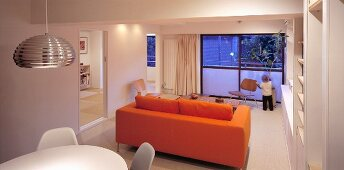 Dining area and orange sofa in a living room in front of a bank of windows