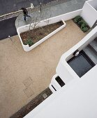 House facade with a view of an outside stairway and beautifully designed forecourt with flower bed and retaining walls