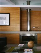 Wood paneled living room wall and built-in chimney with stainless and glass doors