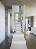 White stair landing in front of stairs in an open living room built of concrete