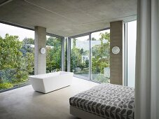 Corner of a sleeping area with free standing bathtub in front of a panoramic window in a contemporary concrete house