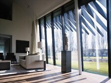 Classic living room with sculpture on a pedestal in front of a modern glass facade and garden view