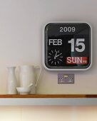 Modern wall clock beside assorted ceramic pitchers on a surface