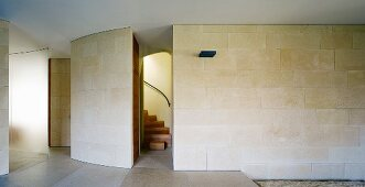 Minimalist, modern lobby with stone tiles on the wall and ceiling high passageway with a view of a stairway