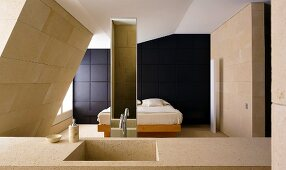 Stone wash basin in a bedroom with a bed in front of a wall clad in black wood