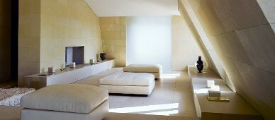Ottomans upholstered in white in a living room under a roof with cubic flooring