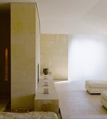 Stone tiles on wall elements in a bright living room and candles on a stone bench