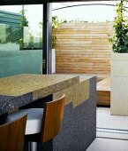 Granite bar with elegant stools in front of an open terrace door and view of a wooden diving wall