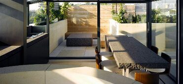 Breakfast bar made of gray stone and bar stools in front of a terrace window and view of a stone block