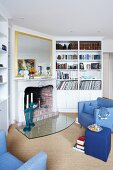 View into a living room with blue furniture, book shelve and fireplace
