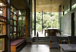 Indian house with traditional wood and glass facade and concrete walls in living room with view of garden