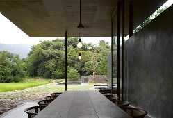 Rustic table on veranda of contemporary house with concrete wall and view into garden