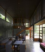 Grey seating in contemporary, open-plan, concrete living room and wood and glass facade with view into garden