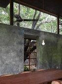 Long wooden table in front of concrete wall with lattice window and transom