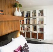 A bed with an upholstered headboard and a contemporary shelf with cubic modules on the wall