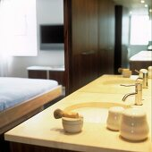A shaving brush and bathing utensils on a modern wash stand in front of a mirror
