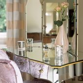 A dressing table with a mirrored surface and a three-way mirror