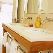 A simple, modern wash stand with two basins and a wall taps