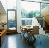 A modern, split-level house - wooden bucket chairs in an open-plan dining room with a terrace