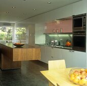 A dining area in front of a free-standing walnut kitchen counter in an open-plan kitchen with white cupboards