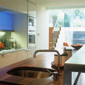 A wooden kitchen work surface with an integrated sink and designer taps