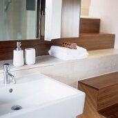 A modern wash basin with bathing utensils on a shelf