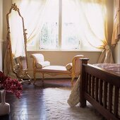 An antique chaise lounge in front of a large floor mirror in a bedroom