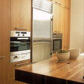 A fitted kitchen with wooden cupboards and a stainless steel fridge