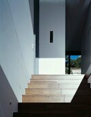 A modern stairway with a play of light and shadow on the wooden steps