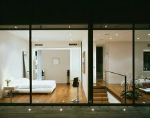 A terrace with floor lights and a view into a modern, illuminated bedroom and a living room
