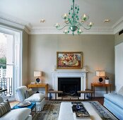 Traditional living room with green glass chandelier and sofas in front of fireplace