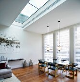 Modern living space with skylight and pendant lamps above dining table and retro leather chairs