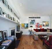 Modern living space with framed pictures on shelves and sofa with scatter cushions