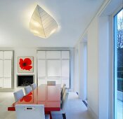 Open-plan dining room with red painted dining table and white upholstered chairs in front of made-to-measure cupboards