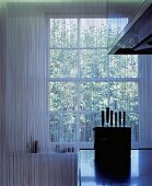 Reflection of transparent cord curtain in the surfaces of a stainless steel kitchen and knife block against the light