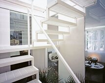 White stairwell with view into modern living room with sphere-shaped chair