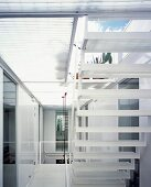 View from below of white clouds in blue sky through light steel stairs and of glass and mesh roof terrace floor