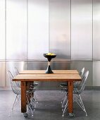 50s-style wire chairs at plain wooden tables on castors in front of stainless steel fitted cupboards