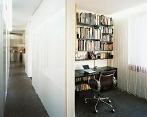 View of long hallway and small office niche with shelving and cord curtain